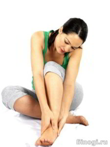 Девушка разминает стопу ноги при симптомах фасцита