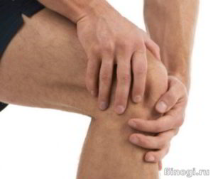 Мужчина спортсмен сжимает руками колено от боли и хруста