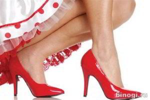 Щиколотки ноги в красных туфлях с высоким каблуком